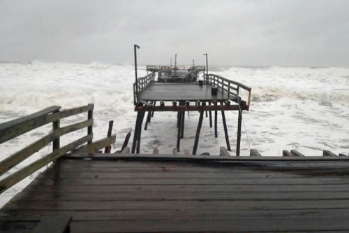 The Outer Banks' Avalon Pier was cut into multiple sections on Monday. But there is a sliver of good news in all of Sandy's misery: a crew of locals, including Hank, Troy, Murph, and Denis, closed off the end section directly in this photo's foreground, shortening the pier but ensuring it will be open for business again. That's what we call American ingenuity in the face of obstacles. Photo: Justin Gizzard