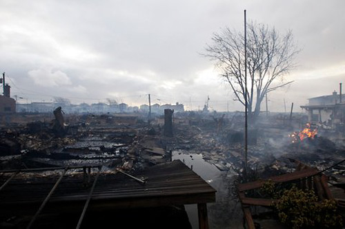 A more pulled-back view of the tragic scene in the Rockaways. Firefighters had a hard time getting the massive blaze under control because the area was also one of the most flooded in all of New York City. Photo: Frank Franklin/li/Associated Press