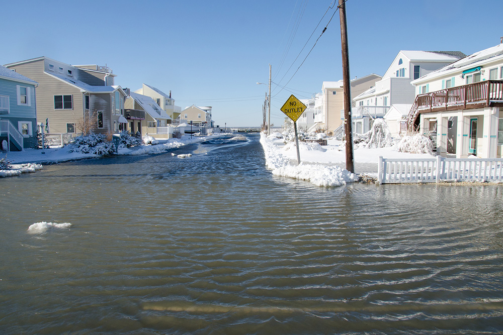 """We must acknowledge something right off the bat; something that we all once knew but forgot along the way: to the casual observer, surfing in a snowstorm is very clearly an insane thing to do."""" Who dares to even cross this New Jersey street? Photo: J. Hall"""