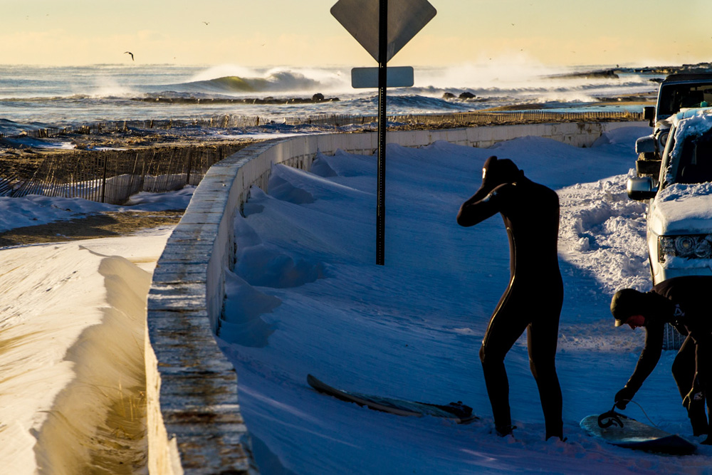 """""""Just take a sip. The first duck-dive in frosty water will hurt a bit. But after that? Bliss. Uncrowded lineups with firing waves."""" These New Jersey surfers know what awaits. Photo: Christor Lukasiewicz"""